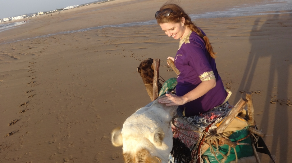 Renee petting a camel on the beach in Essaouira, Morocco.