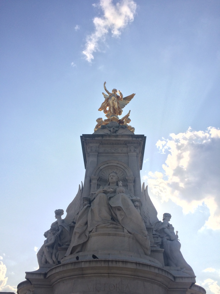 A dramatic image of the Queen Victoria statue in front of Buckingham Palace.