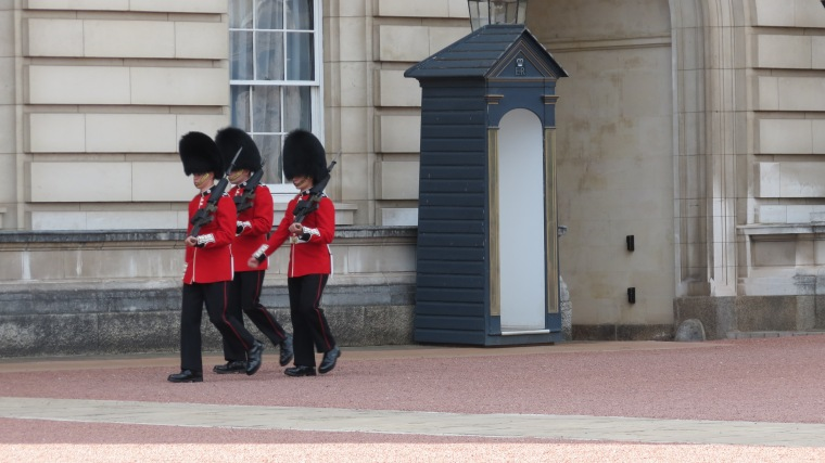 Thee of the Queen's Guards dressed in red coats and furry bear hats march in front of Buckingham Palace