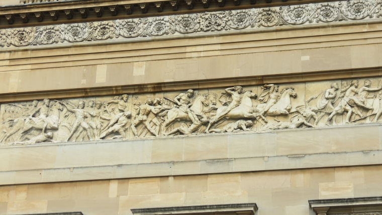 Intricate stone carvings of men on war horses in battle adorn the outside of Buckingham Palace.