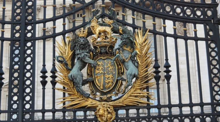 A lion and unicorn surround the Royal Crest on an ornate gate at the front of Buckingham Palace.